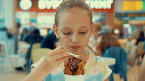 Cute teenager girl eating ice cream in food court. Young girl teenager enjoying Archivo
