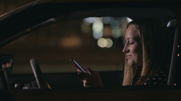 Charming woman texting message on cellphone in car Footage