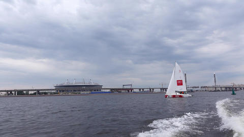 POV rush away from white sailing dinghy, white sail against cloudy sky Footage