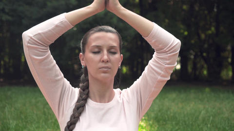 A pregnant woman practices yoga in the park, sitting in a lotus position Footage