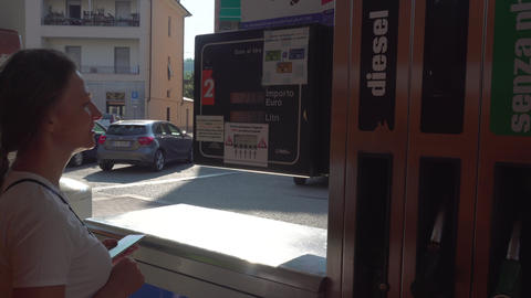 Woman looks at pricing panel at italian filling station Live Action