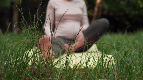 Pregnant woman doing yoga in the park on the carpet, grouping in a pose Footage