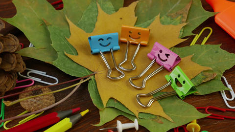 Smiles Binder Clips on Yellow Fallen Maple Leaves and School Office Supplies Footage