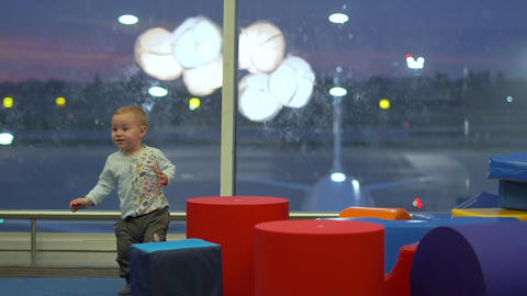 Smiling cute boy playing with big cubes in a children's play area at the airport Live Action