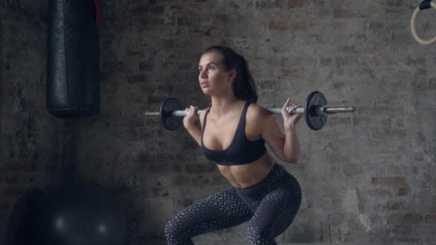 Young lady in black sportswear doing squats with barbell. Strength and Live Action
