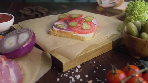Chef's hand adds sliced bacon to the sandwich with tomatoes and pickles, cooking Footage
