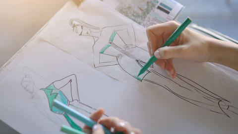 The hand of the designer with a pen, designing and sketching clothes collection Live Action