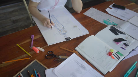 Female designer with a pen, designing and sketching new collection Live Action
