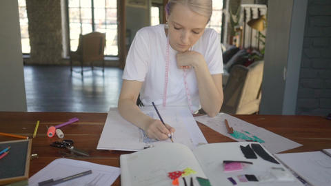 Young fashion woman designer drawing design sketch working in her manufacturing Live Action