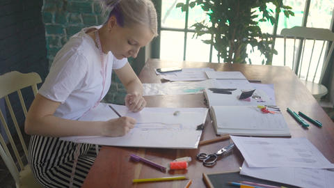 Female designer with a pen, designing and sketching new collection Footage