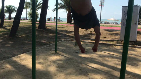 fitness time, Sportive Man Doing Trick on the Horizontal Bar, hanging top feet Live Action