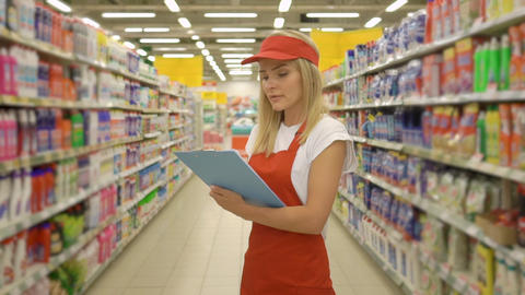 Pretty hardware store worker holding clipboard and standing among shelfs in Live Action