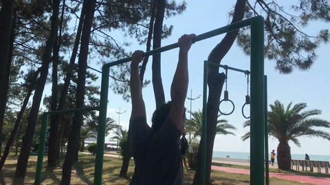 fitness time, Sportive Man Doing Trick on the Horizontal Bar, pull up Live Action