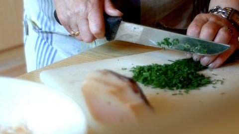 lady chops chives for the preparation of Tyrolean dumplings Footage