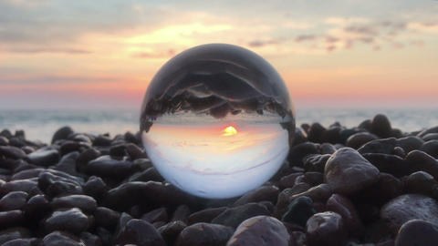 Loop cinemagraph crystal ball on the beach stones sunset, wonderful landscape Footage