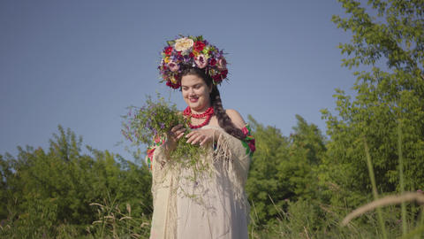 Beautiful overweight woman with a wreath on her head sniffing flowers on the Live Action