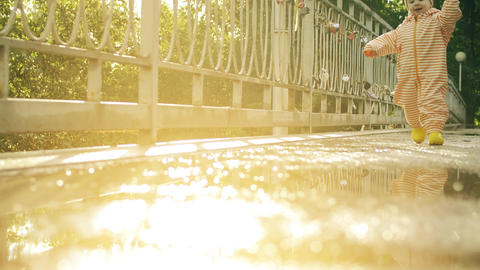 Happy baby girl in orange waterproof raincoat and rubber rain boots walking on Footage