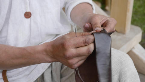 Close up male hands sewing needle leather clothes. Craftsman sewing leather Footage
