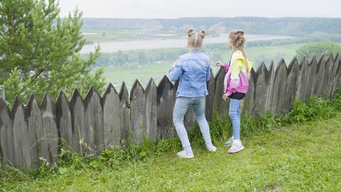 Two teenage girls stand by the wooden fence looking into distance. Girls Footage