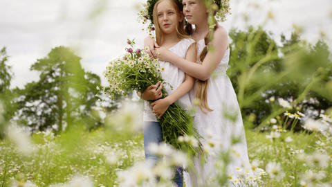 Two girl teenager in floral wreath with flowers bouquet standing on blooming Footage