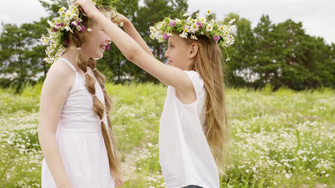 Two girl wearing floral wreath having fun on blooming meadow at summer day Footage