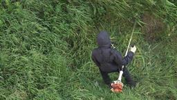 Gardener cutting green grass manual gasoline lawn trimmer in garden. Zoom in Footage