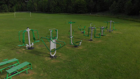 Flyover of outdoor exercise equipment in a field (V455) Live Action
