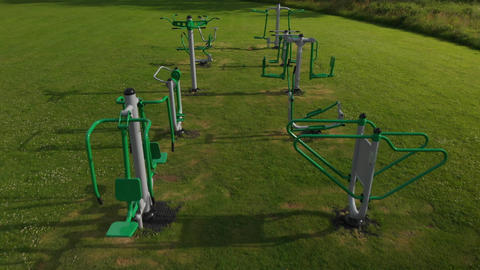 Flyover of outdoor exercise equipment in a field (V458) Live Action