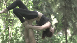 Girl doing yoga with a guy who holds her in the air. Slow motion Footage