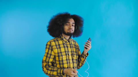 Positive African American man using phone to listening music in his headphones Footage
