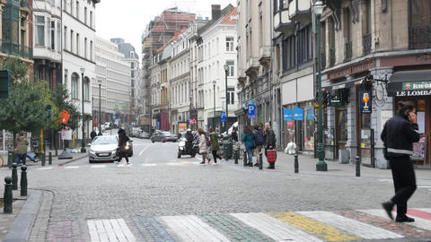 Young man with the phone crosses pedestrian crossing in Brussels Live Action