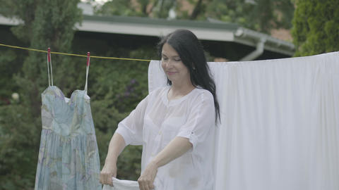 Attractive senior woman with long hair black hair hanging white clothes on a Live Action