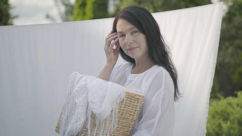 Adorable mature woman with long black hair holding wicker basket in hands while Live Action