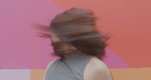 Asian young adult female swinging hair in front of colourful background Live Action