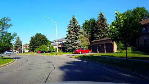 Driving Around a Bend of Residential City Road With Lush Trees During Summer Day. Driver Point of Footage