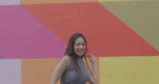 Asian young adult female dancing and jumping happy in front of colourful background Live Action