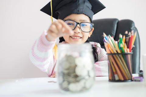 Little Asian girl wearing graduate hat putting the coin into clear glass jar 012 フォト