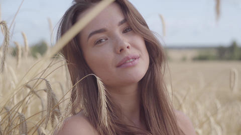 Portrait carefree woman enjoying nature and sunlight in wheat field at Footage