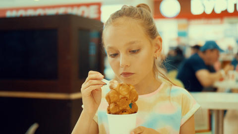 Teen girl eats tasty dessert ice cream with bubble waffles in cafe Footage