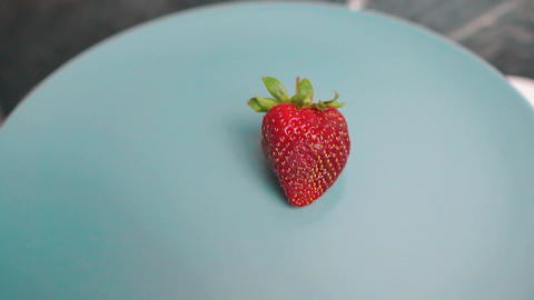 One single red strawberry rotating on grey background Live Action