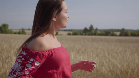 Side view of beautiful carefree woman with long hair running through the wheat Footage