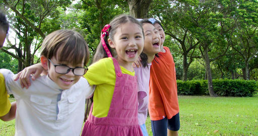 Multi-ethnic group of school children laughing and embracing Live Action