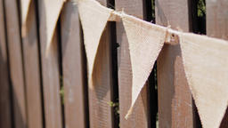 Festive Garland of Triangle Linen Flags on Wooden Fence at Summer Day on Holiday Footage