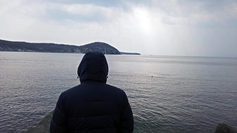 A man in a blue jacket with a hood looking at the seascape Footage