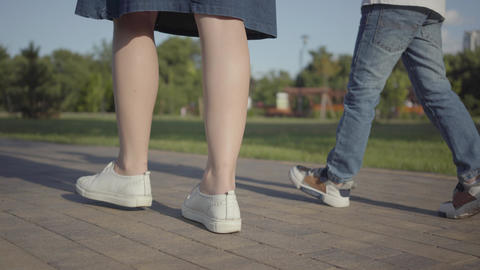 Close-up legs of siblings children walking holding hands in the summer park Footage