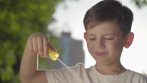 Portrait of the carefree boy blowing soap bubbles and smiling at the camera in Footage