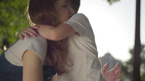 Older sister hugging with younger brother outdoors. Slow motion Live Action