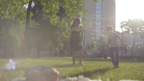 Older sister playing with younger brother in the summer park. Leisure outdoors Footage