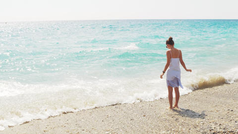 Beautiful attractive woman standing on the beach. Girl on blue Mediterranean sea Footage