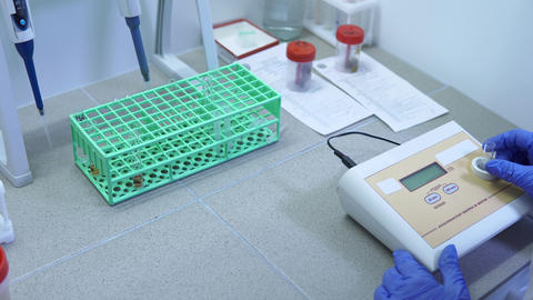 Laboratory technician checks tests from test tubes on special equipment Footage